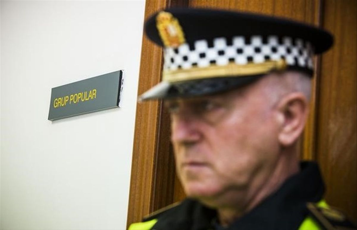 Un policía custodia las dependencias del grupo popular en el Ayuntamiento de Valencia, mientras agentes de la Guardia Civil efectúan un registro.