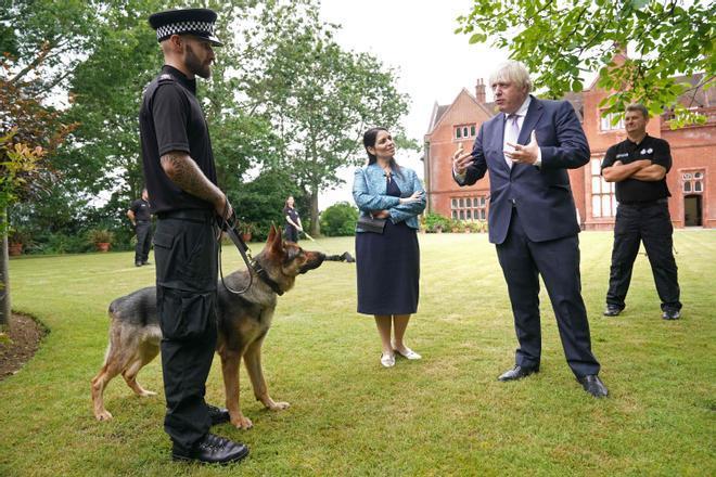 Boris Johnson y la secretaria de Vivienda, Priti Patel, departen con un agente durante una visita a la comisaría de la policía de Surrey en Guildford el pasado 27 de julio.