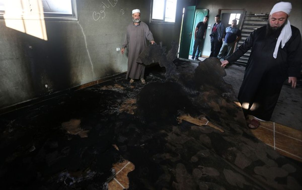 Un grupo de Palestinos musulmanes examina los daños causado por el incendio en la mezquita en Aqraba.