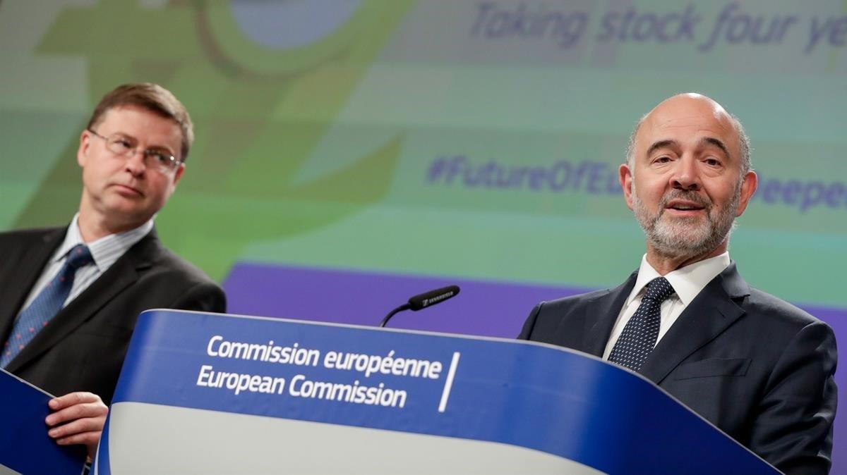 Dombroivskis (izquierda) y el comisario de Asuntos Económicos, Pierre Moscovici.