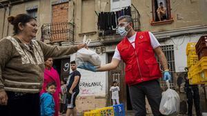 Un voluntario de la Cruz Roja entrega una bolsa con alimentos en un núcleo de infraviviendas en València