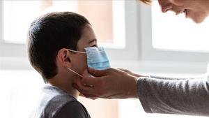 Una madre coloca a su hijo una mascarilla para evitar el contagio de coronavirus