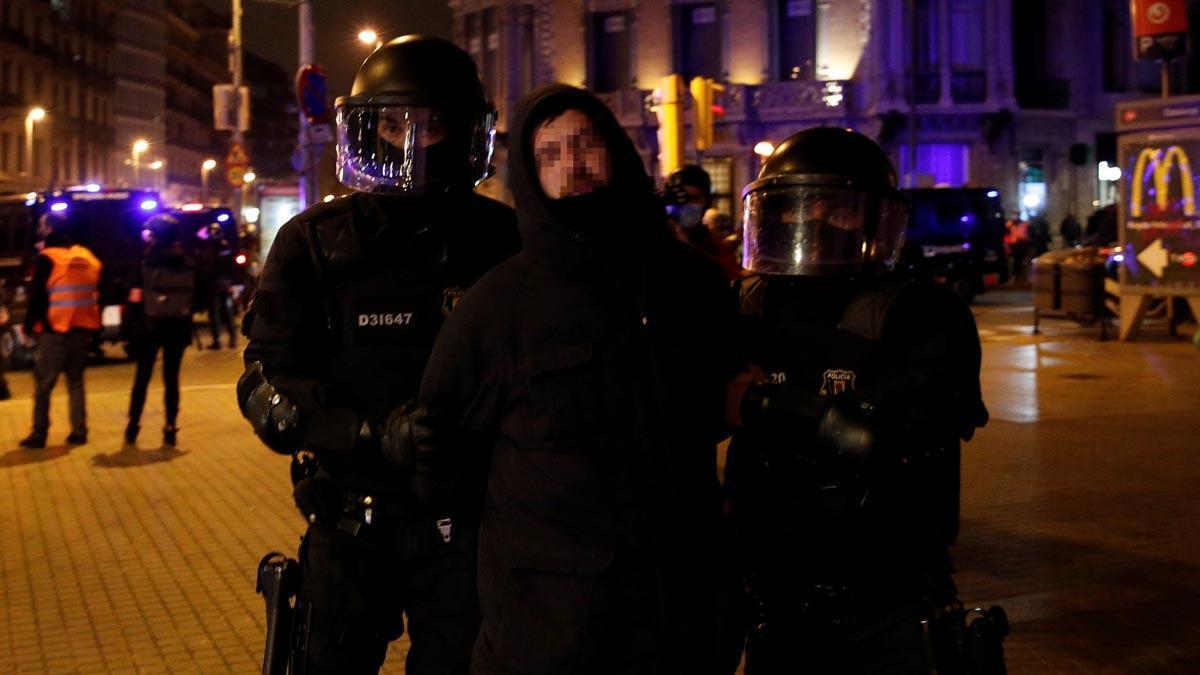Seis noches de disturbios en Barcelona en protestas contra la detención de Pablo Hasél. En la foto, agentes de los Mossos se llevan a un detenido.