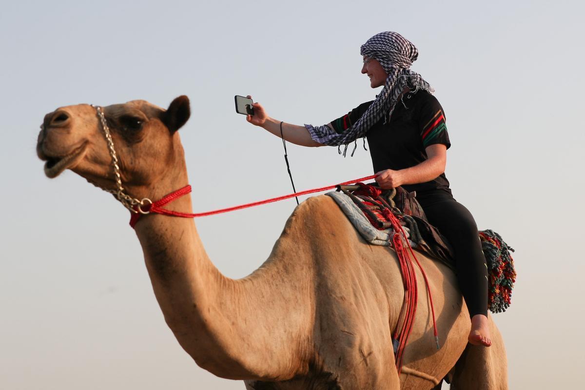 Sarah Collins monta en camello por el desierto emiratí.