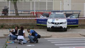 La policía científica, buscando balas y muestras de sangre delante del tanatorio de Gavà después del tiroteo.