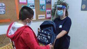 Entrega de una mochila con material escolar a un estudiante vulnerable.