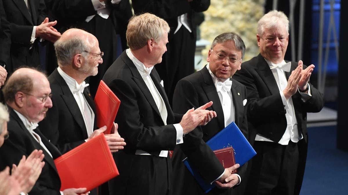 El Nobel de Literatura del 2017, Kazuo Ishiguro (el segundo por la derecha), flanqueado, de izquierda a derecha, por los galardonados en Medicina (Jeffrey Hall, Michael Rosbash y Michael Young) y Economía (Richard Thaler), en la ceremonia de entrega de los premios en Estocolmo.