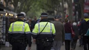 Dos miembros de la Guardia Urbana de Barcelona patrullan por las Ramblas de la ciudad