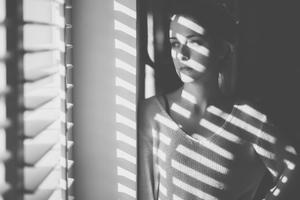 Mujer frente a la ventana en su casa