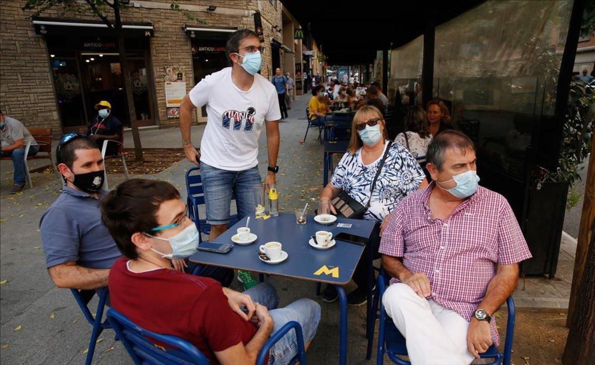 Un grupo de personas con mascarilla toma algo en una terraza de Barcelona.