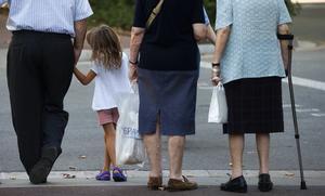 Tres personas de edad avanzada pasean con una niña por Barcelona.