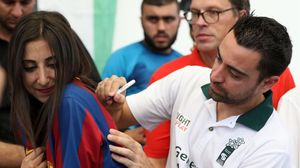 Xavi firma un autógrafo en la camiseta de una joven, este jueves en el campo de refugiados de Baqa.