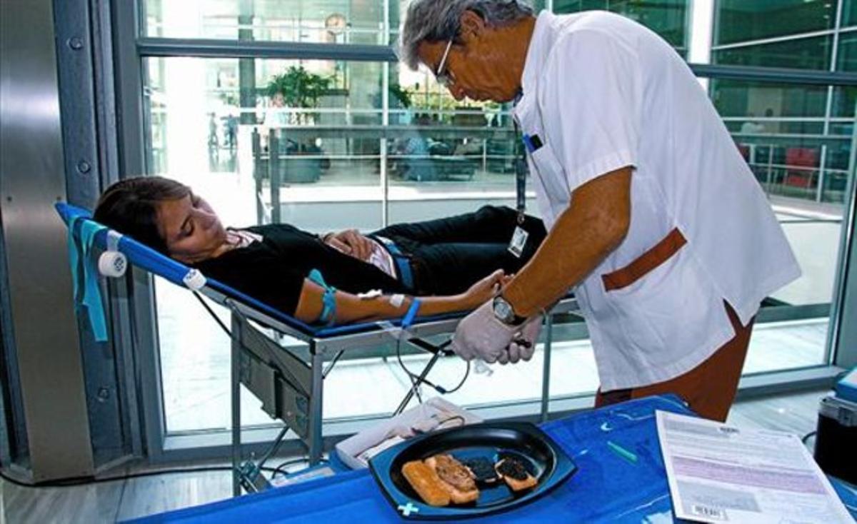 El enfermero Gabriel pincha a la joven Clara mientras las tapitas la esperan, ayer en el hospital de Sant Pau.