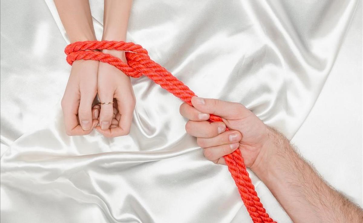 Un hombre ata con una cuerda las manos de una mujer.