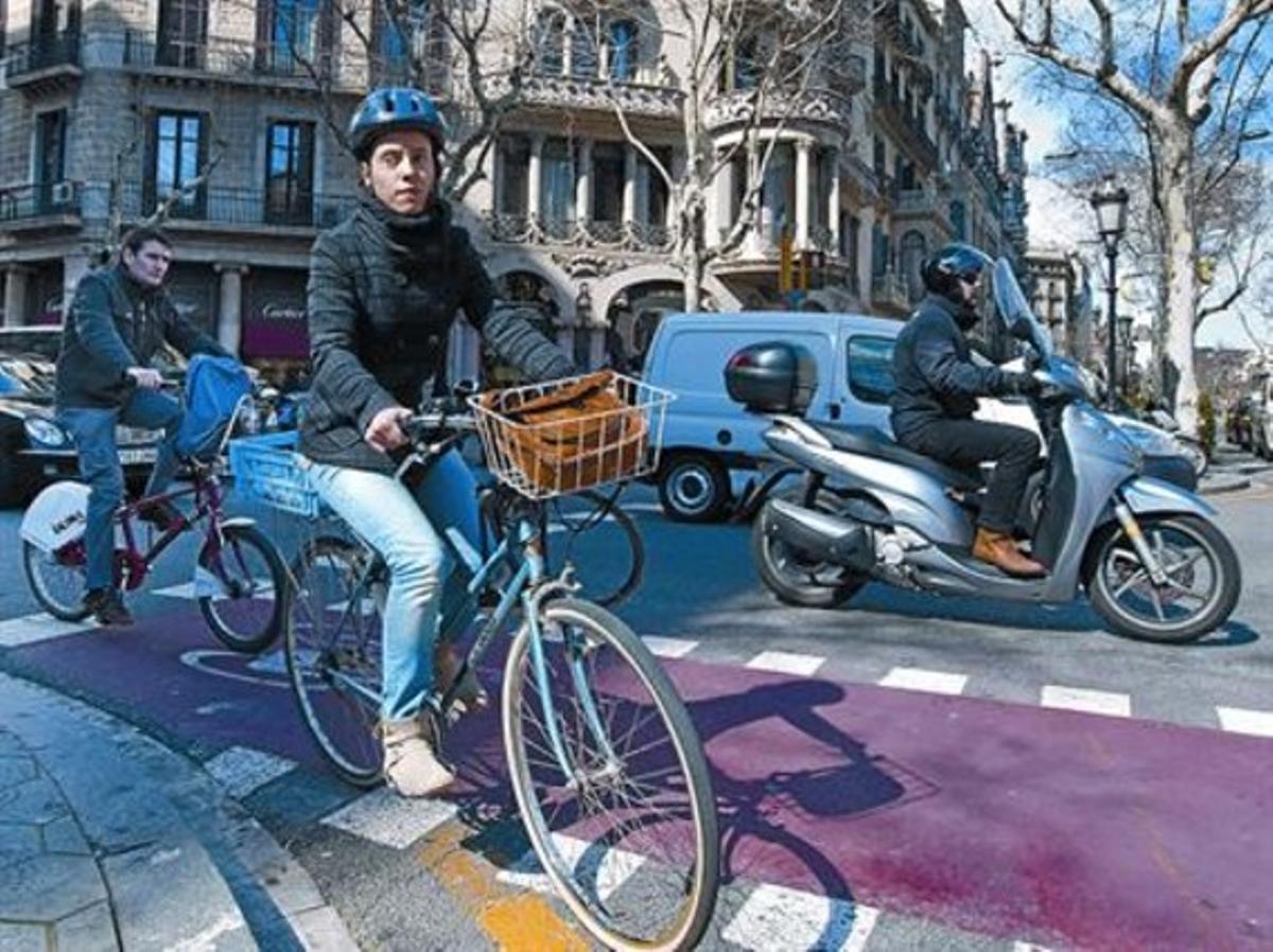Una ciclista con casco y otro sin, ayer en Consell de Cent con paseo de Gràcia.