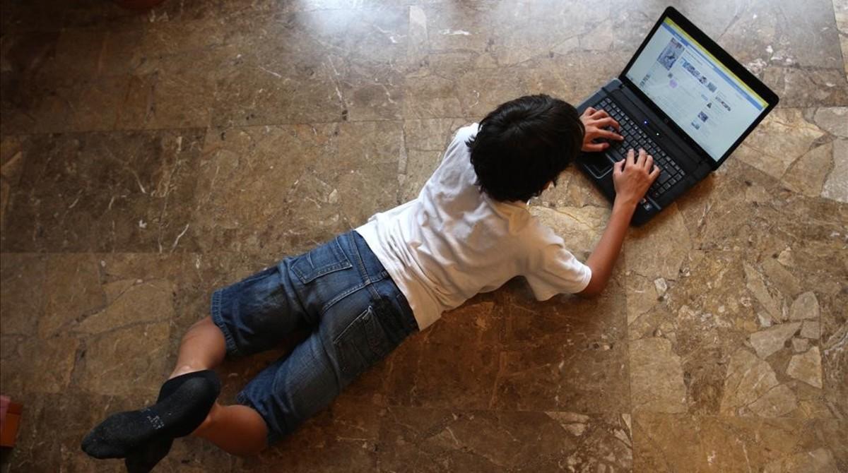 Un niño navega por internet tumbado en el suelo de su casa.