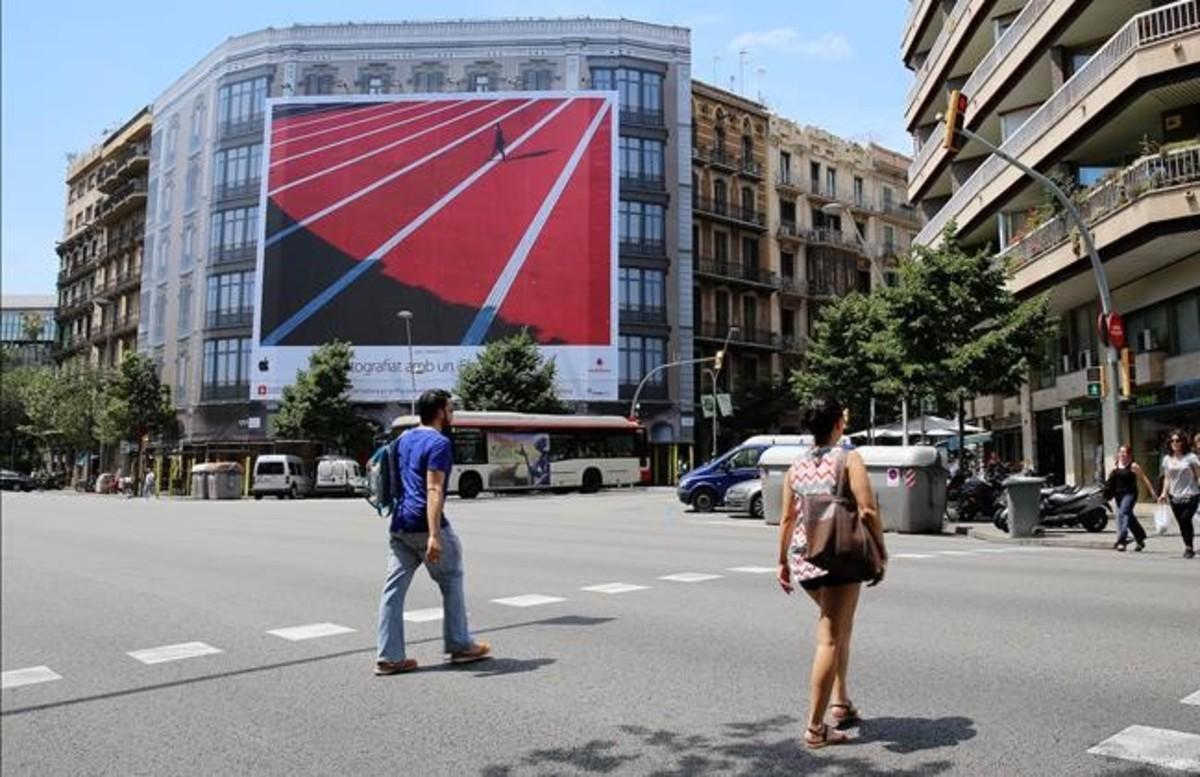 Una lona cubre la rehabilitación de un edificio en la esquina de la calle Balmes con Aragó.