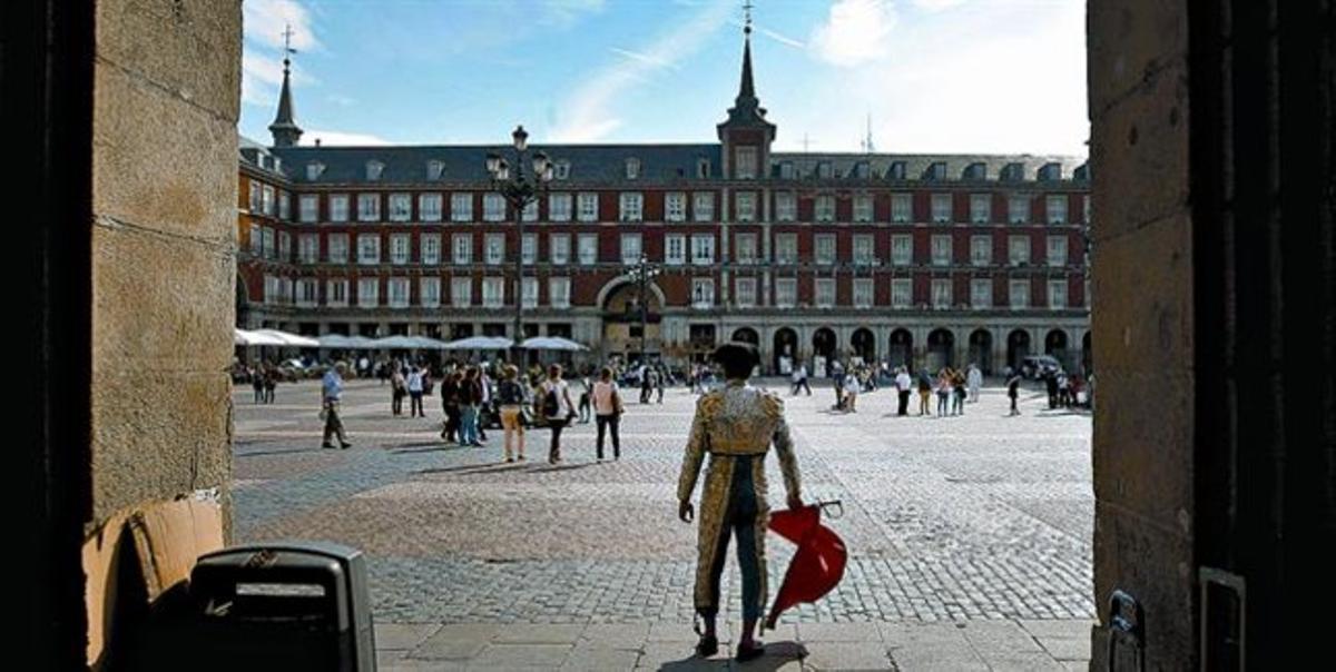 Un hombre vestido de torero intenta atraer la atención de los turistas en la plaza Mayor de Madrid, el viernes.