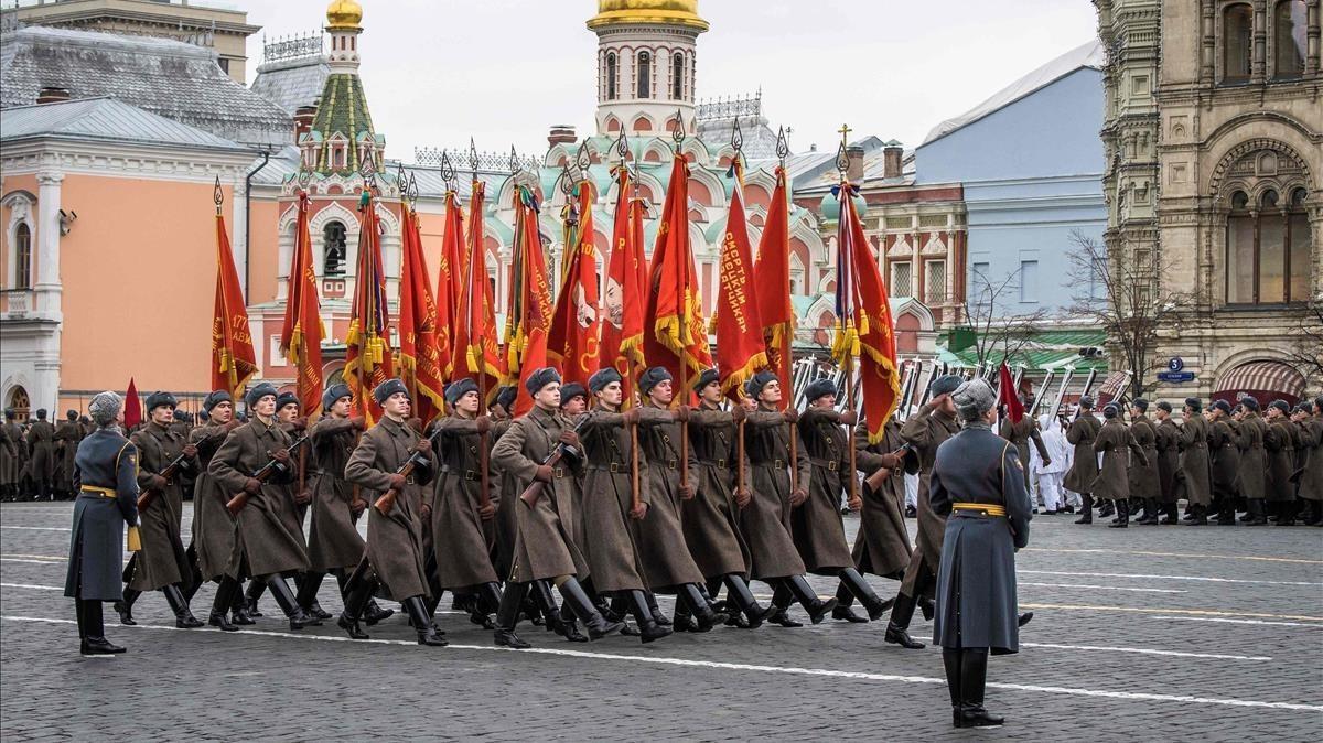 Militares rusos vestidos con uniformes históricos marchan durante el desfile militar.