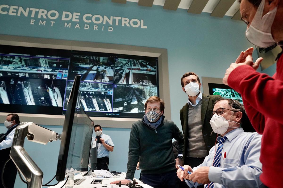 Pablo Casado y José Luis Martínez-Almeida atienden las explicaciones de los trabajadores de la Empresa Municipal de Transportes (EMT) de Madrid.