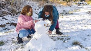 Unas niñas juegan con la nieve en el puerto de Àger (Noguera), este lunes.