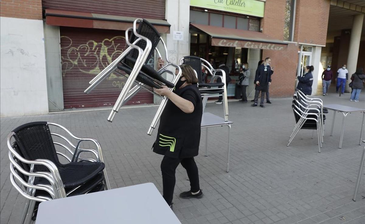 Una trabajadora de un bar del Poblenou recoge las mesas de la terraza tras acabarse el horario en el que puede servir desayunos.