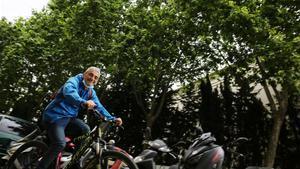 Un ciclista pasa por delante de una frondosa y, en primavera, irritante hilera de plátanos de Barcelona