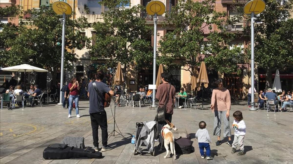 Nicolás (a la derecha, con su perra Almendra) e Iván, tocan chacareras, un género argentino, en la plaza del Sol.