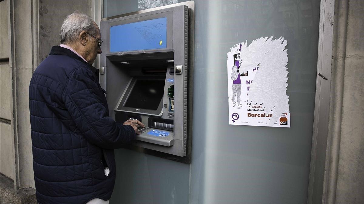 Un pensionista saca dinero de un cajero automático de una entidad bancaria de Barcelona.