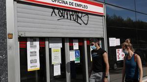 Dos jóvenes pasan ante una oficina de empleo en Madrid, el pasado 5 de mayo.