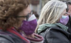 Dos mujeres con doble mascarilla en un acto electoral en Barcelona, el 30 de enero