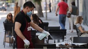 El paro baja en septiembre en 26.329 personas, su mayor descenso desde 1996. En la foto, un camarero desinfecta una mesa de una terraza en Madrid, el pasado 29 de julio.