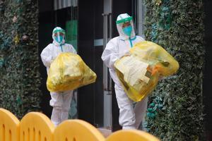 Dos personas con el equipo de protección completo contra el coronavirus en el exterior del hotel donde se han alojado en Wuhan los investigadores de la OMS.
