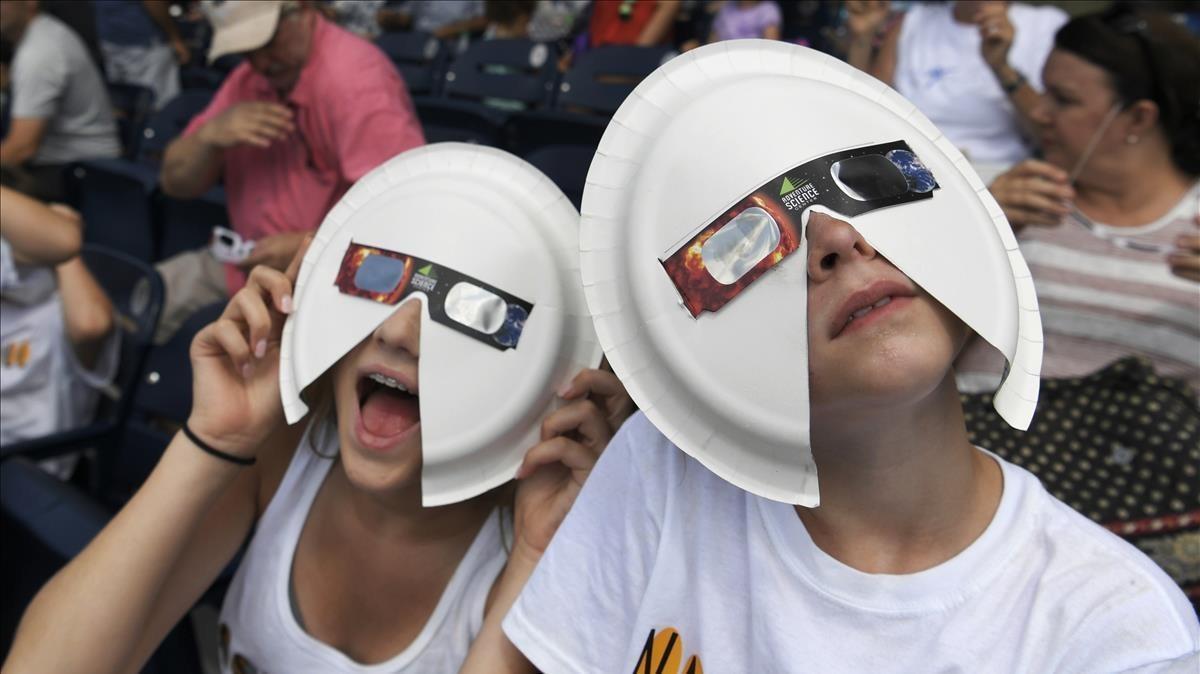 Dos observadores, durante un festival astronómico en Nashville, una de las pocas ciudades en las que fueposible observar el eclipse como total.