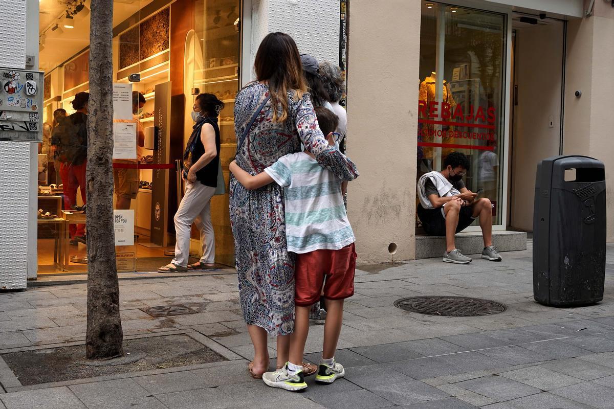 Importado de EEUU, la hiperpaternidad es un fenómeno que implica la sobreprotección de los hijos, en la imagen un niño abraza a su madre a la espera de entrar a un comercio en la calle Fuencarral en Madrid.