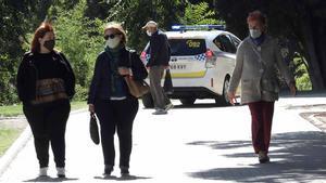 Primeras horas de las nuevas restricciones en Madrid. En la foto, un coche de policía patrulla por un parque del barrio madrileño de Aluche.