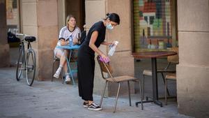 Una camarera limpia varias sillas y una mesa de la terraza de un bar de Barcelona, el pasado 26 de mayo.
