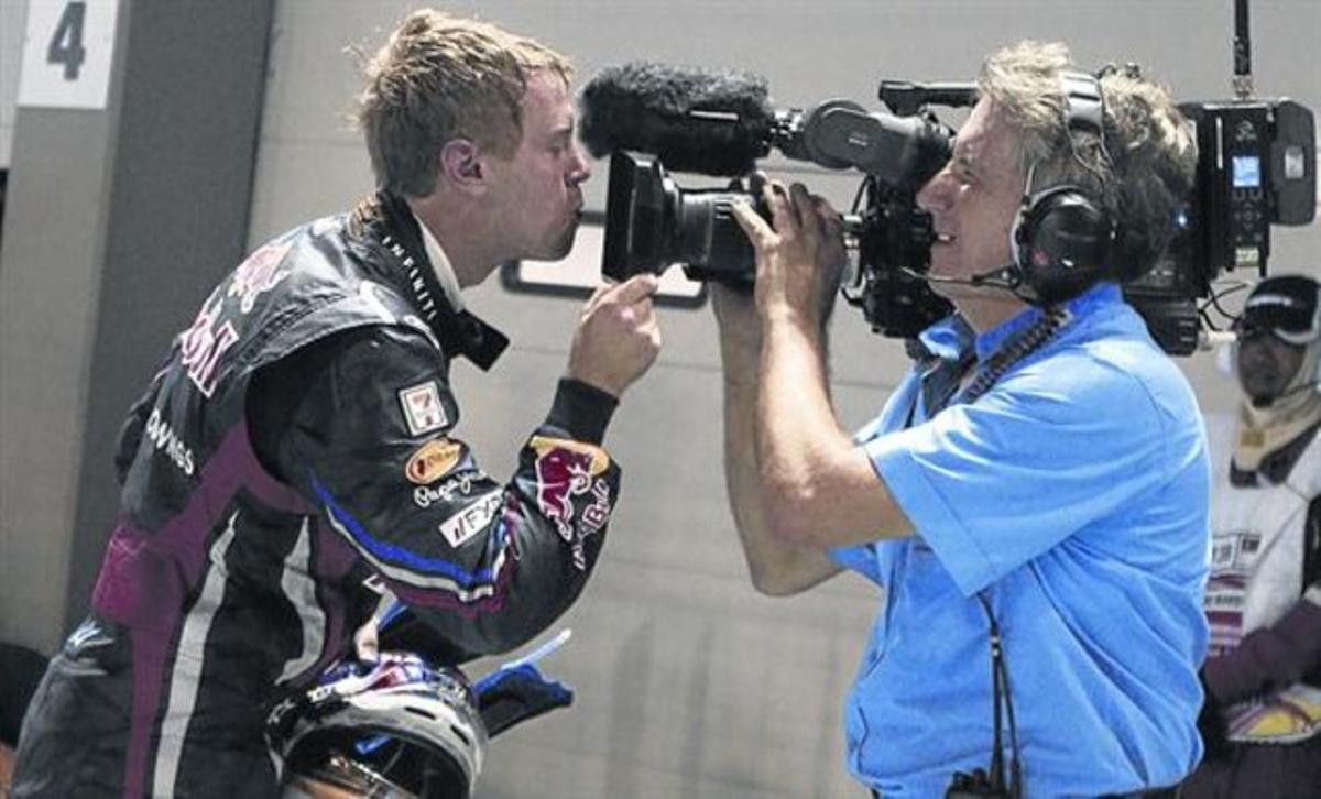 El tetracampeón alemán Sebastian Vettel besa el objetivo de una cámara del Mundial de F-1 tras ganar el GP de Singapur del 2011.