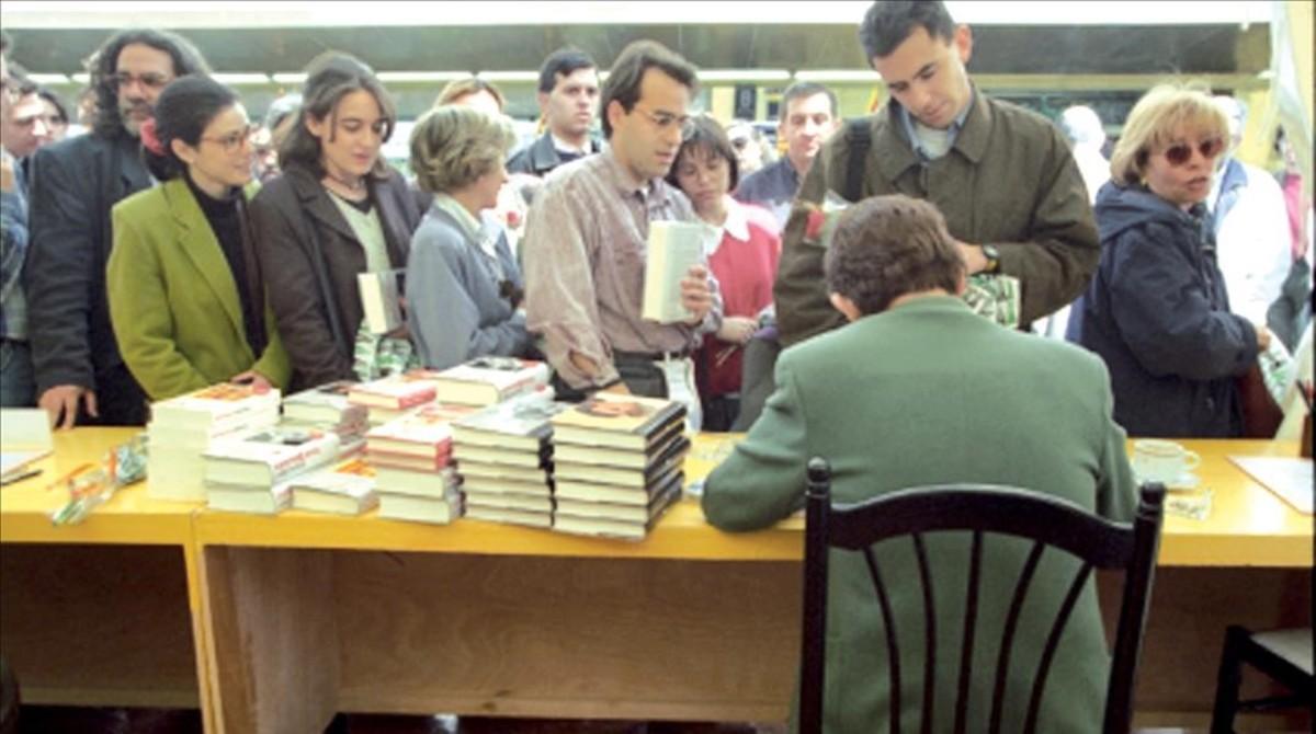 Terenci Moix (de espaldas) firma libros el día de SantJordi de 1995.