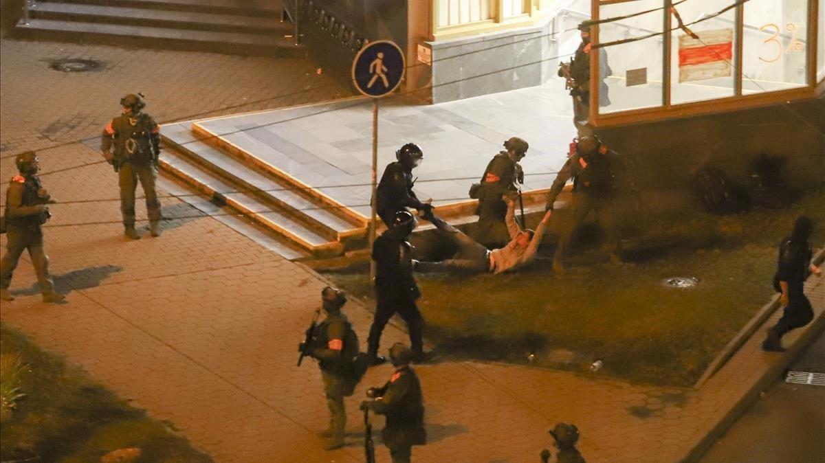 La policía antidisturbios se lleba arrastras a un manifestantes en Minks-