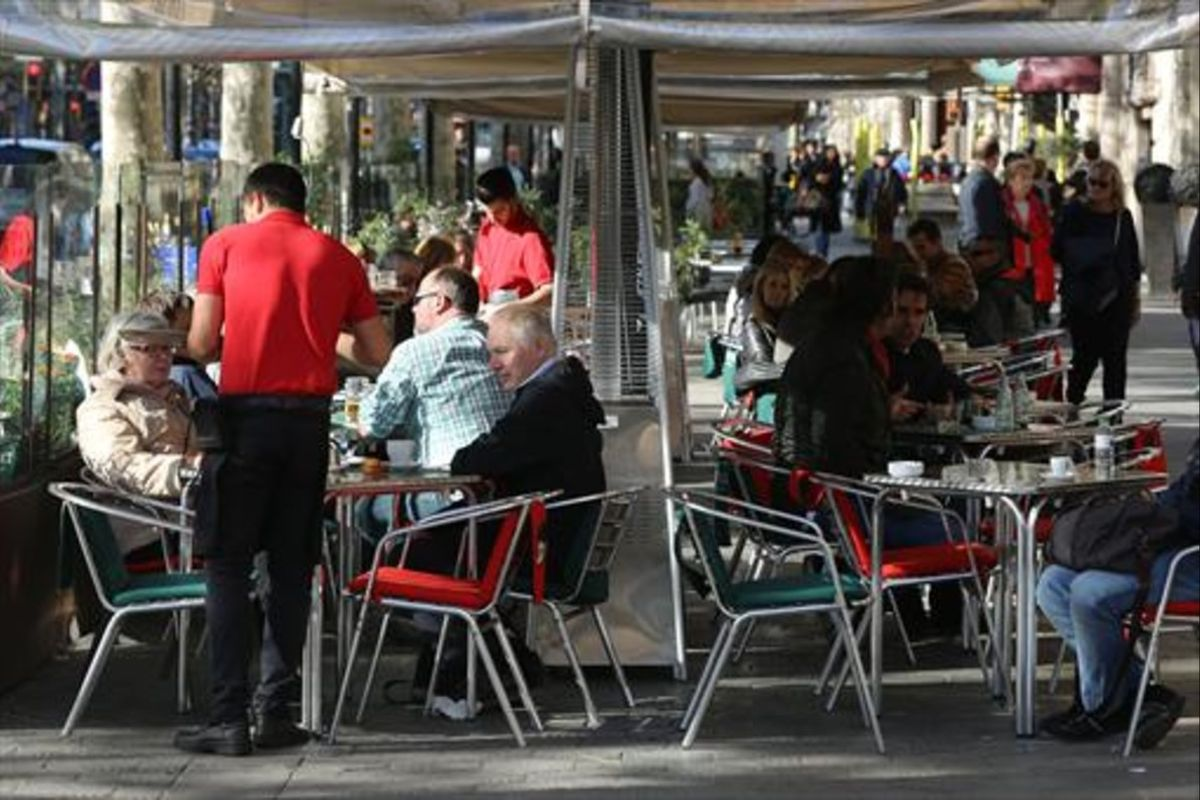Varios camareros sirven a clientes en terrazas de bares del paseo de Gràcia.