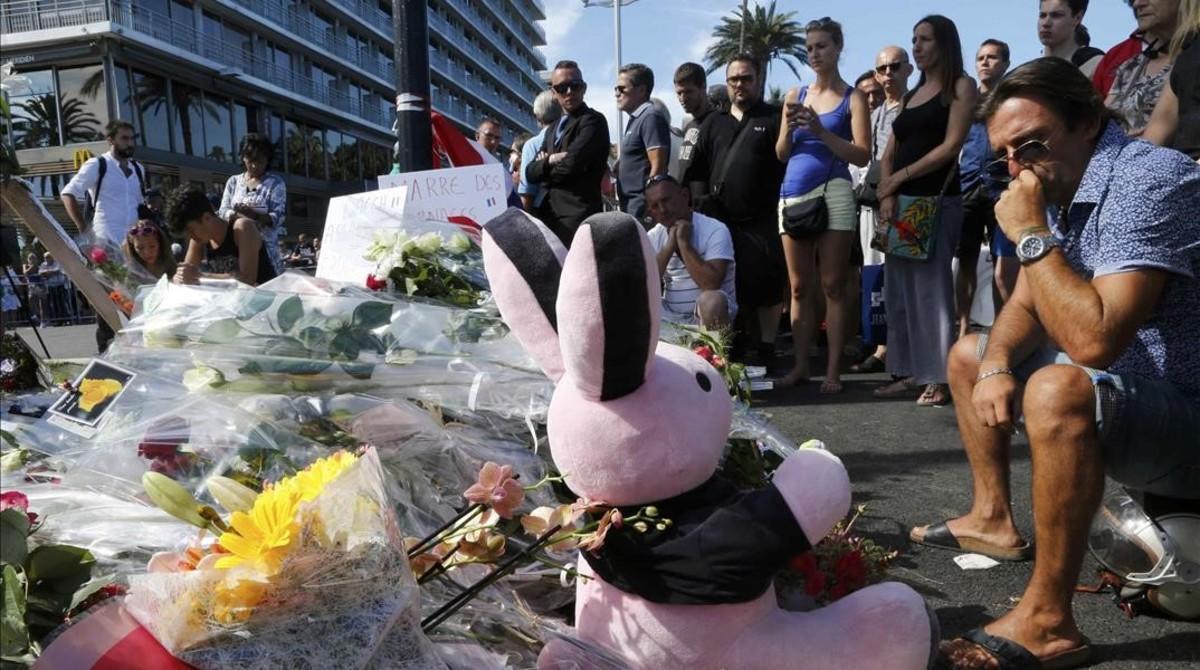 Varias personas colocan flores, velas y un peluche en tributo a las víctimas del atentado en Niza, este viernes.