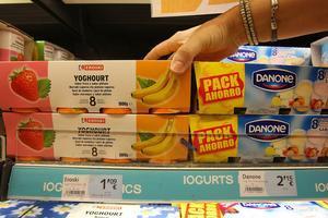Una consumidora compara productos de marca blanca y de marca tradicional.