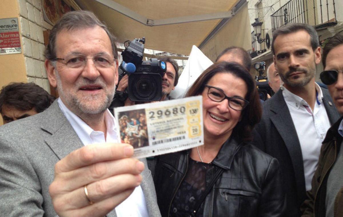 Mariano Rajoy recibe un décimo de lotería durante su recorrido porEstepona (Málaga).