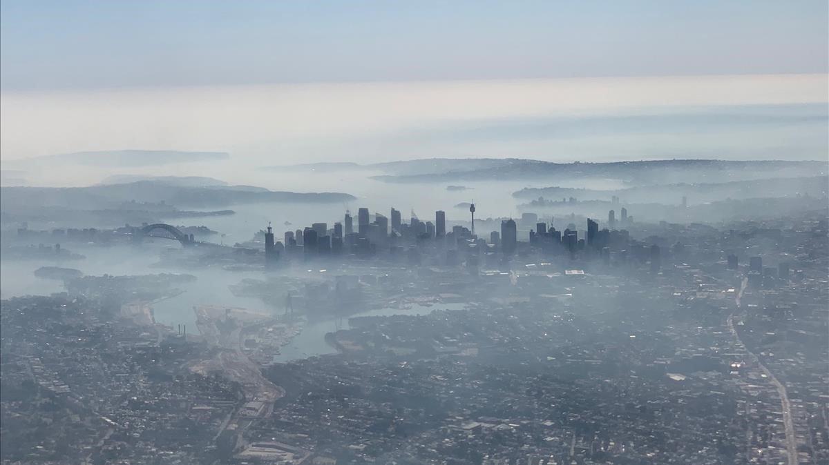Imagen aérea de la ciudad de Sídney cubierta por una densa nube de humo blanco, este martes.