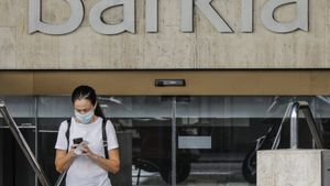 Una mujer sale de la sede de Bankia en Valencia