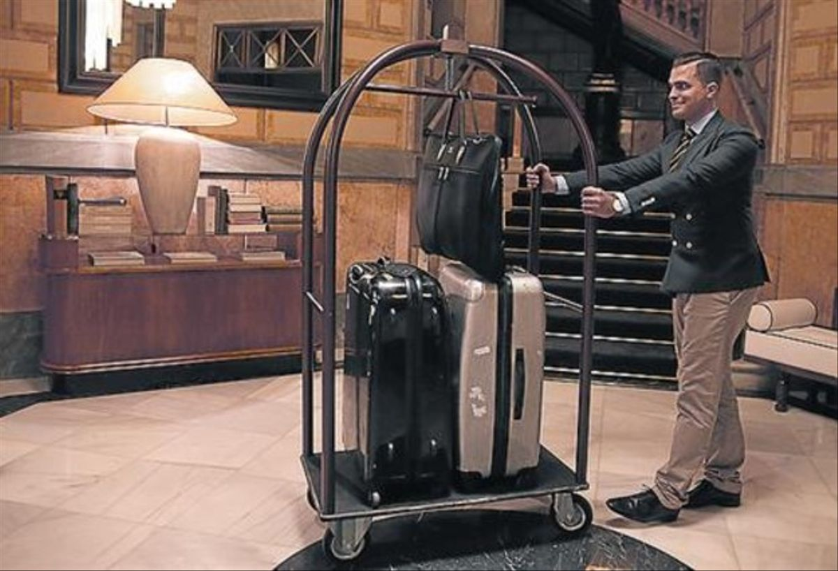 Rubén lleva unas maletas a un huésped llegado de noche.