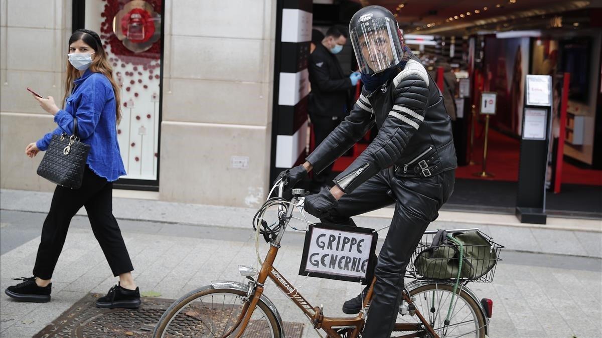 Un hombre monta su bicicleta con un cartel que dice gripe general, en la avenidaChampsElysee.