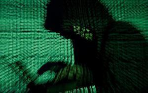 Un hombre trabaja con un portátil mientras sobre él se proyecta un código informático.