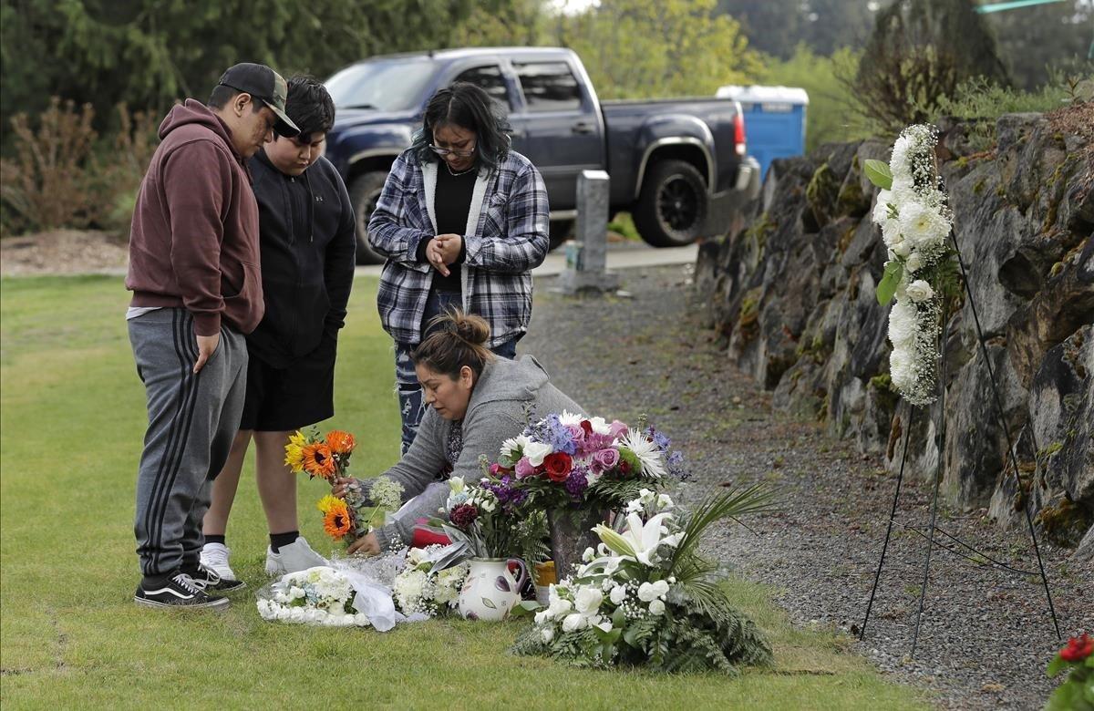 Antonia López, deposita unas flores en la tumba de su esposo, quien murió de COVID-19 a los 44 años.